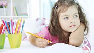 little girl thinking what to draw, colorful pencils