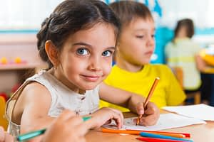 Group of cute little prescool kids drawing with colorful pencils
